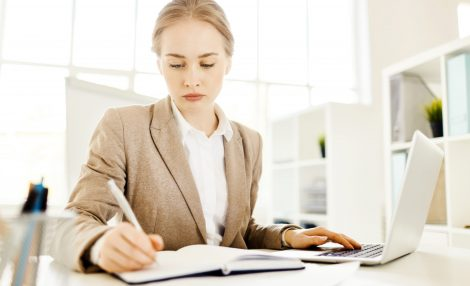 Young female analyst making notes in notebook while analyzing online data