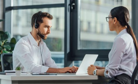 professional male translator working online with laptop and headset on meeting with businesswoman